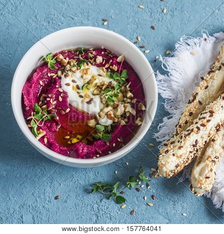 Beet hummus. Delicious appetizer or snack. On a blue background