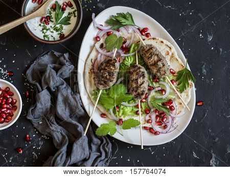 Lamb kebab on flatbread with lettuce onions and pomegranate. On a dark background top view