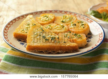 Plate with tasty garlic French bread slices on wooden table