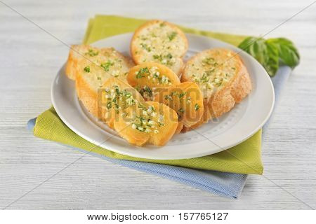 Plate with tasty garlic French bread slices and green napkin