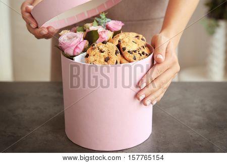 Female florist preparing box with beautiful flowers and cookies, closeup