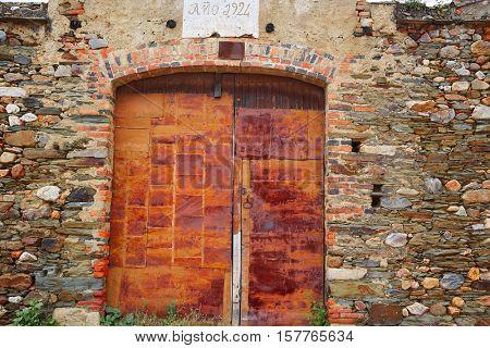 Old grunge iron rusted door along Via de la Plata way in spain