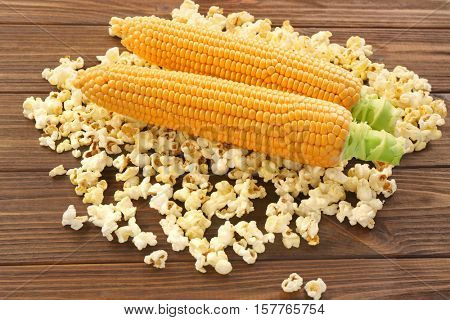 Fresh maize and popcorn on wooden background