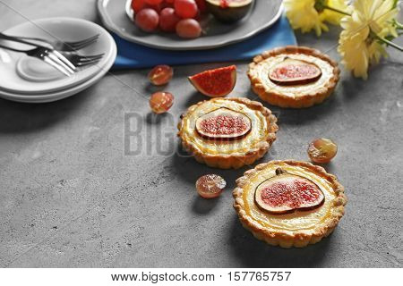 Tasty fig cakes with grapes and fresh flowers on grey background