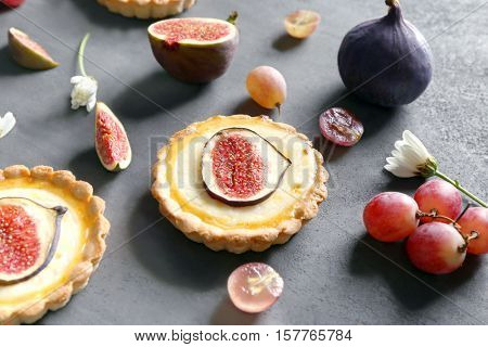 Tasty fig cakes with fresh grapes on grey background