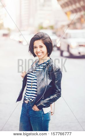 Portrait of beautiful smiling young Caucasian latino girl woman with dark brown eyes and short dark hair in blue jeans leather biker jacket in city street toned with filters