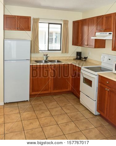 Kitchen with wooden cabinets fridge and electric stove