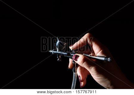 female hand holding the airbrush in the dark