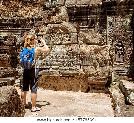 Tourist Photographing Bas-reliefs In Temple. Angkor, Cambodia
