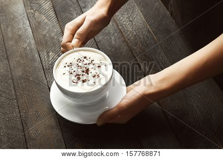 Female hands holding cup of tasty coffee with ice-cream on wooden background