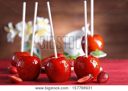 Candy apples with strawberry on red wooden table