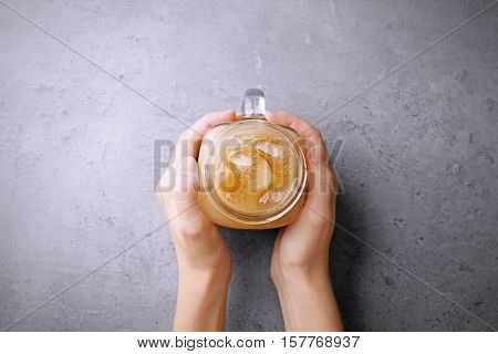 Woman holding glass cup of iced coffee with milk on grey background
