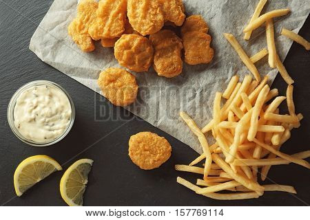 Tasty nuggets with fries and sauce on table