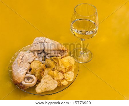 A photo of a squid sandwich, traditional Madrid snack, with a glass of white wine, on a vibrant yellow background, with copyspace