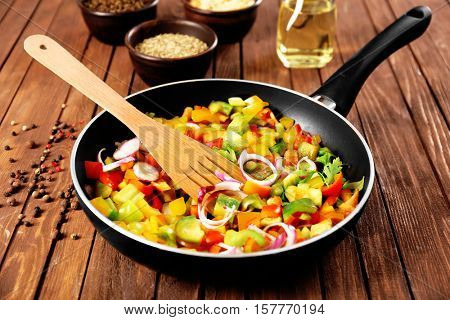 Frying pan with chopped bell pepper and onion on wooden background