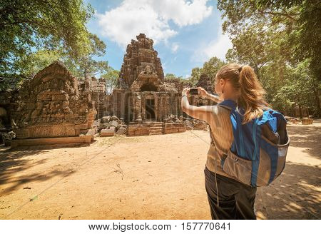 Tourist Photographing Entrance To The Temple In Angkor, Cambodia