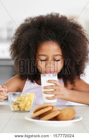Pretty African-American girl drinking milk with pleasure at breakfast in the kitchen