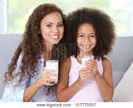 African-American mother and daughter drinking milk and sitting on the couch