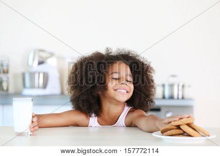 Curly African-American girl preferring cookies instead of milk for breakfast