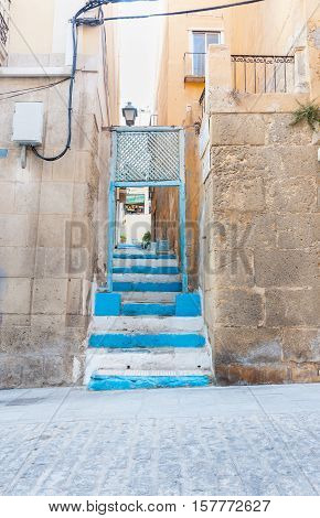 Blue steps in narrow alleyway leading up to window of home on next street Alicante Spain street and building scene