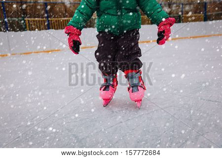 litte girl learning to skate on ice in winter snow