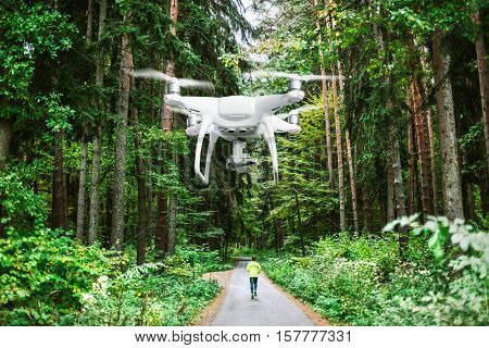 Hovering drone taking pictures of man running on a path in old green forest.