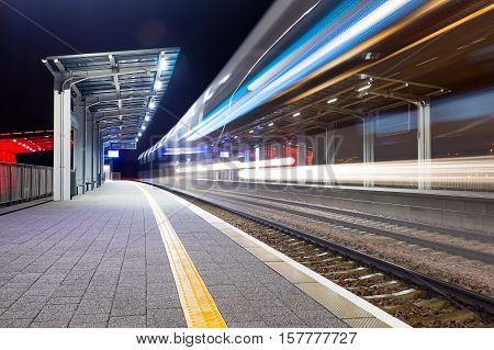 Modern railway train station at night. Bright colors and rapid blurred movement. Fast pace business abstract concept.