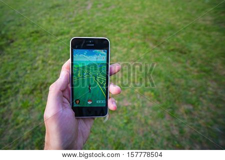 Buenos Aires, Argentina - Nov 11, 2016: Apple iPhone 5c held in one hand showing its screen with Pokemon Go application. Grass on the background.