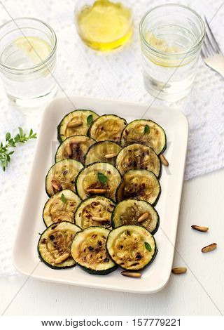 Antipasto of grilled courgette zucchini with olive oil pine nuts and herbs