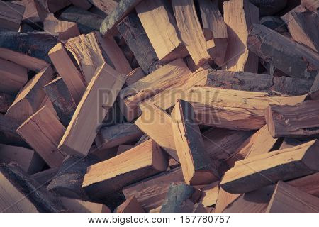 Firewood background - chopped firewood on a stack. Retro style.