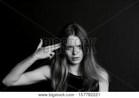 Beautiful long haired girl. The gesture of fingers the gun