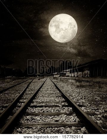 Beautiful countryside Railroad with Milky Way star in night skies full moon - Retro style artwork with vintage color tone (Black and white vintage film grain filter effect styles)