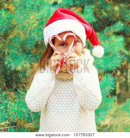 Christmas Child Little Girl In Santa Red Hat Playing With Sweet Lollipop Cane Near A Tree