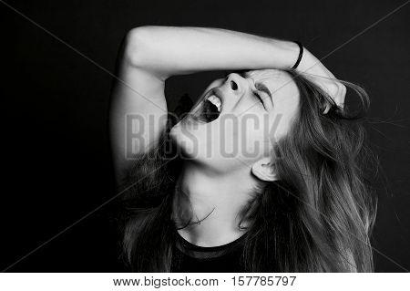 Beautiful girl with long hair yells. Black-white