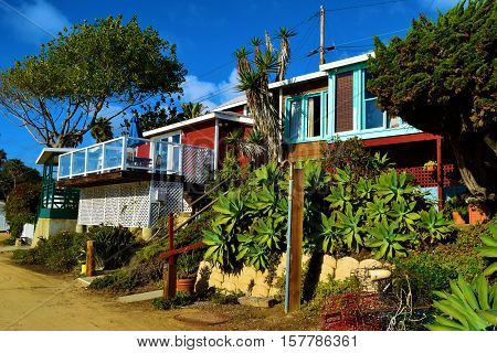 Rustic style beach cottages surrounded by lush green gardens taken at Crystal Cove Beach, CA