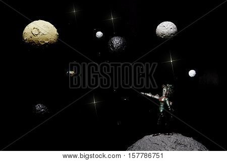 Creature from outer space. A model depicting a solitary extraterrestrial alien life form looking out through space and planets. The alien is pointing towards Earth.