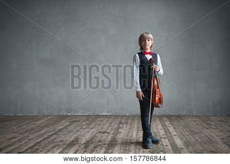Child with violin in studio