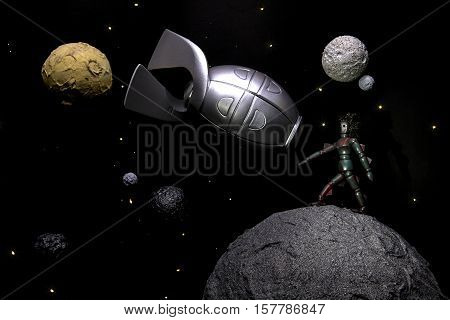 Space explorer. Model showing an alien life form and a space rocket amongst planets and stars in space. A retro B movie style image with many connotations relating to astronomy and space exploration.