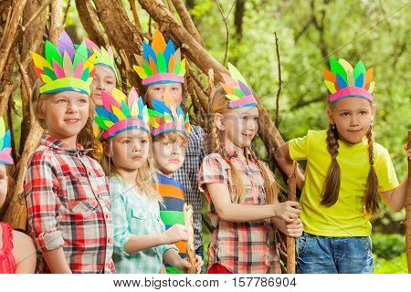 Big group of happy boys and girls, playing Red Indians standing next to the wigwam