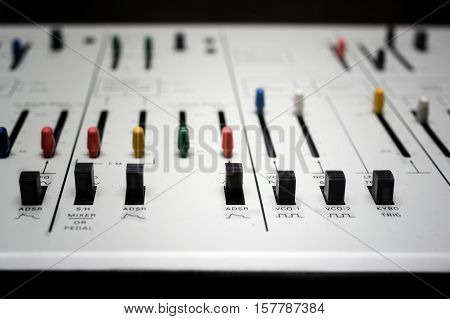 Closeup of a front panel of retro synthesizer extremely shallow depth of field