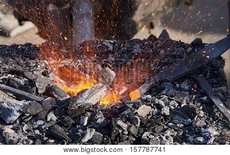 The heating of metal billets on hot coals before forging