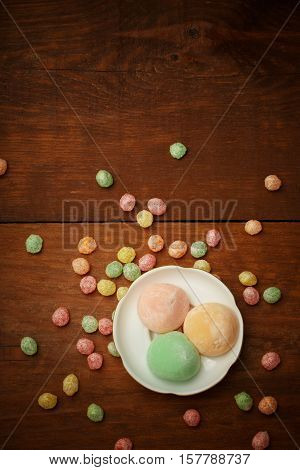 Beautiful colorful japanese mochi rice cakes on white plate at brown wooden table with red yellow green and orange fruit candy drops around