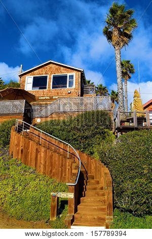 House on top of a bluff with an outdoor staircase in the backyard leading to a beach