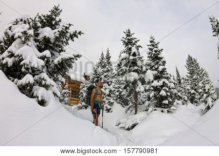 Male Tourist With A Backpack, With A Naked Torso And Legs Is Among The Snowdrifts And Trees