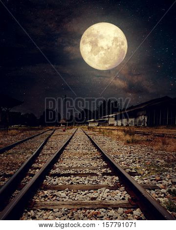 Beautiful countryside Railroad with Milky Way star in night skies full moon - Retro style artwork with vintage color tone (Elements of this moon image furnished by NASA)