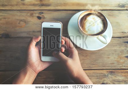Close up of beautiful young hipster woman's hands holding mobile smart phone with hot coffee cup at cafe shop female using cell telephone with blank copy space screen for your advertising text message. vintage color tone
