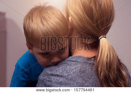 Young blonde woman comforting her little son. Mother and child hugging after quarrel.