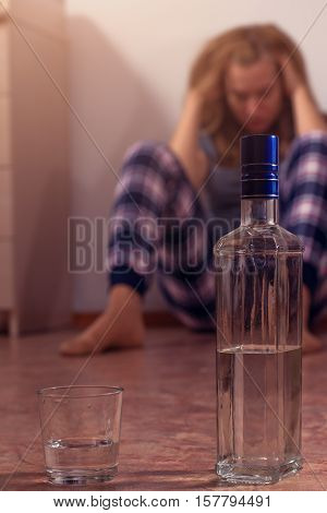 Young caucasian drunk woman sitting on the floor. Alcohol abuse. Bottle and glass shallow depth of field.
