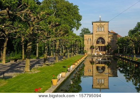 Stuttgart Germany - MAI 13 2015: the Zoo Wilhelma in Stuttgart. Artificial pond with aquatic plants. Ancient palace in the background.