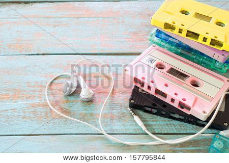 Top view (above) shot of retro tape cassette with earphone heart shape on wood table. Love music concept - vintage pastel color effect styles